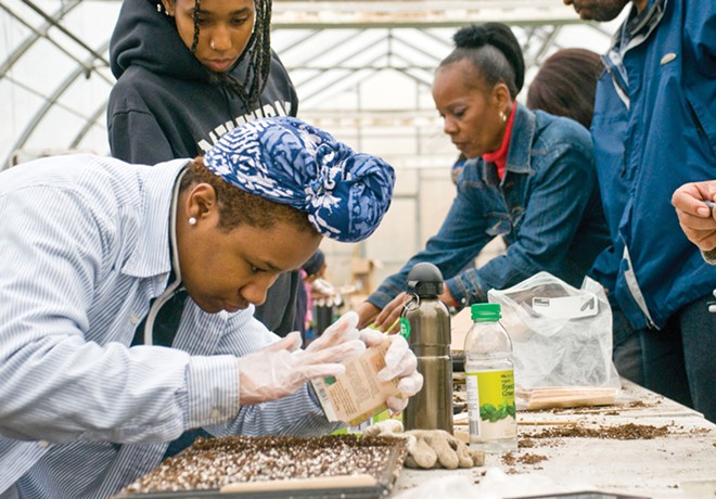 Students in Nerfer Ra Barber's EAT program at Earthworks Farms work on picking out and planting seedlings in early April. - TOM PERKINS