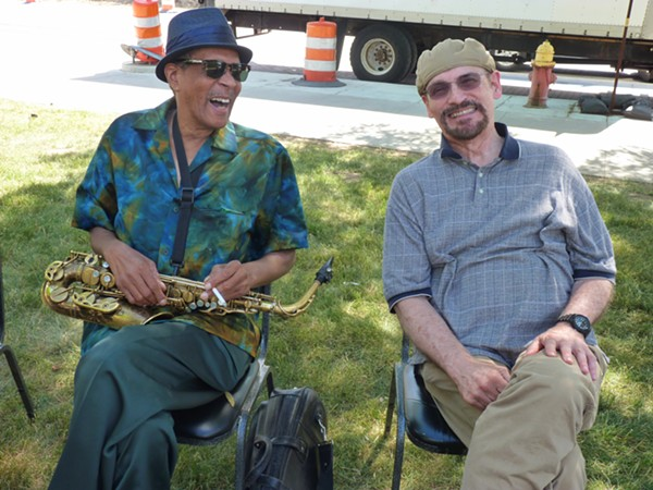 SAX PLAYER LARRY SMITH ON THE LEFT, SEATED WITH UNIDENTIFIED SMILING PERSON, AT 2016'S MAKE MUSIC DETROIT. PHOTO BY NANCY GILLILAND.