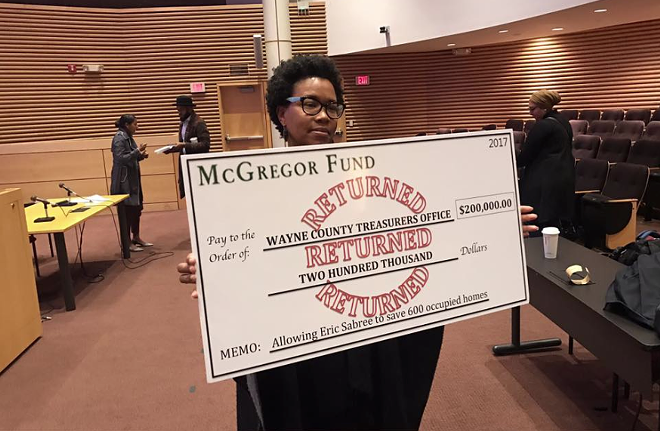 "A housing advocate holds a mock ""returned"" check to the McGregor Foundation. The fund had hoped it could help save 600 occupied homes from the Wayne County tax foreclosure auction this year, but the treasurer rejected the plan, citing its timing. - JERRY PAFFENDORF"