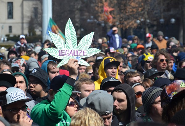 """A man holds up a """"Legalize"""" sign at the 43rd annual Hash Bash rally in Ann Arbor."""