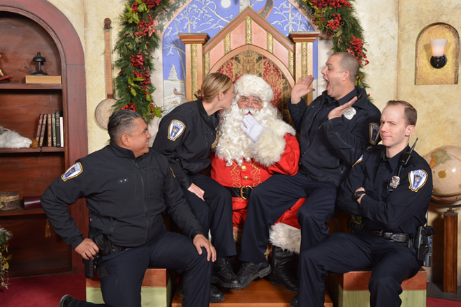 Troy police officers cozy up  to Santa Claus in a photo posted to the department's Twitter account. - TROY POLICE DEPARTMENT