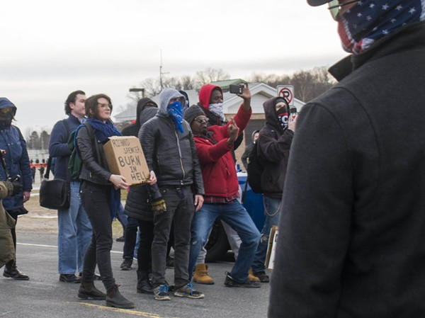 A protester flicks off members of the Traditionalist Worker Party, a neo-Nazi group. - TOM PERKINS