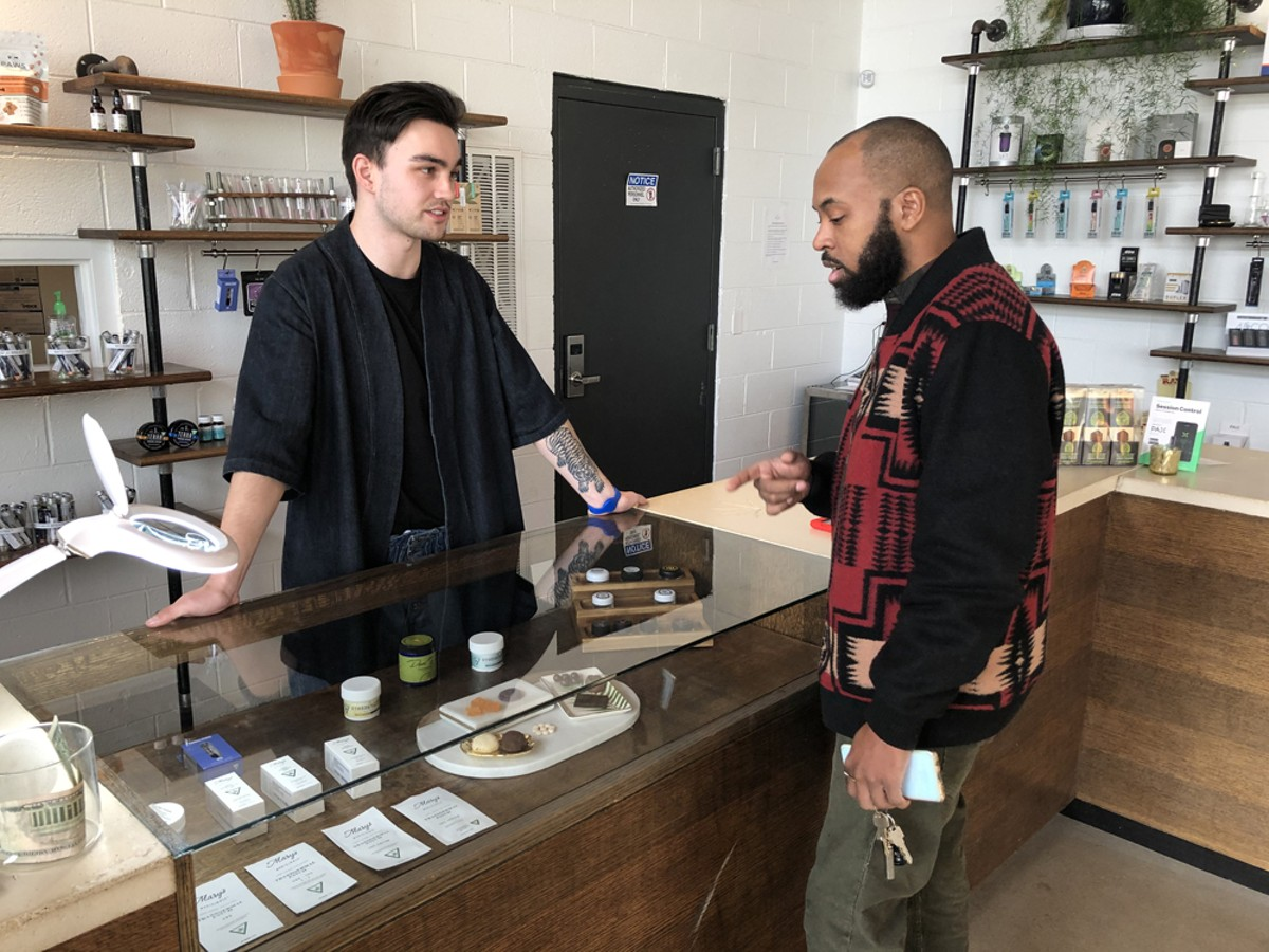A budtender helps a customer at Detroit's BotaniQ.