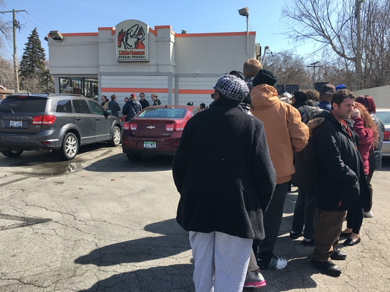 A line snakes around the parking lot of the Little Caesars in Ferndale ahead of Monday's free lunch combo promo. - MIRIAM MARINI