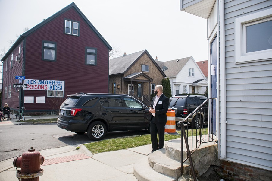 A sign reminding Snyder of his misdeeds hangs across the street from the Polka Dot bar (right) in which Snyder is meeting with local leaders. - TOM PERKINS