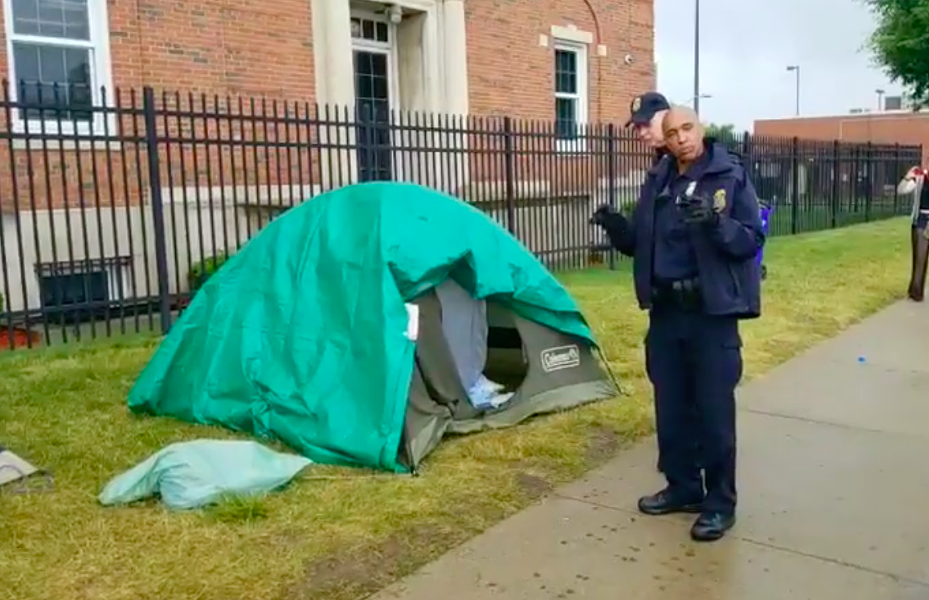 An officer with Homeland Security's Federal Protective Services Police prepares to take down the remaining tents in Detroit's Occupy ICE encampment. - METRO DETROIT POLITICAL ACTION NETWORK