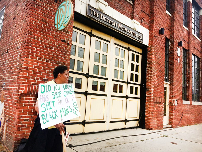 A protester outside Detroit Mercantile on Saturday. - TOM PERKINS