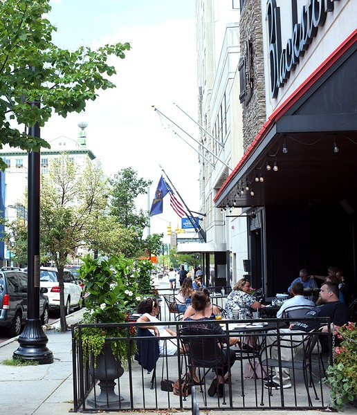 Lunchtime diners hang out on the outdoor patio at Blackstone's Pub& Grill in downtown Flint. - SCOTT ATKINSON