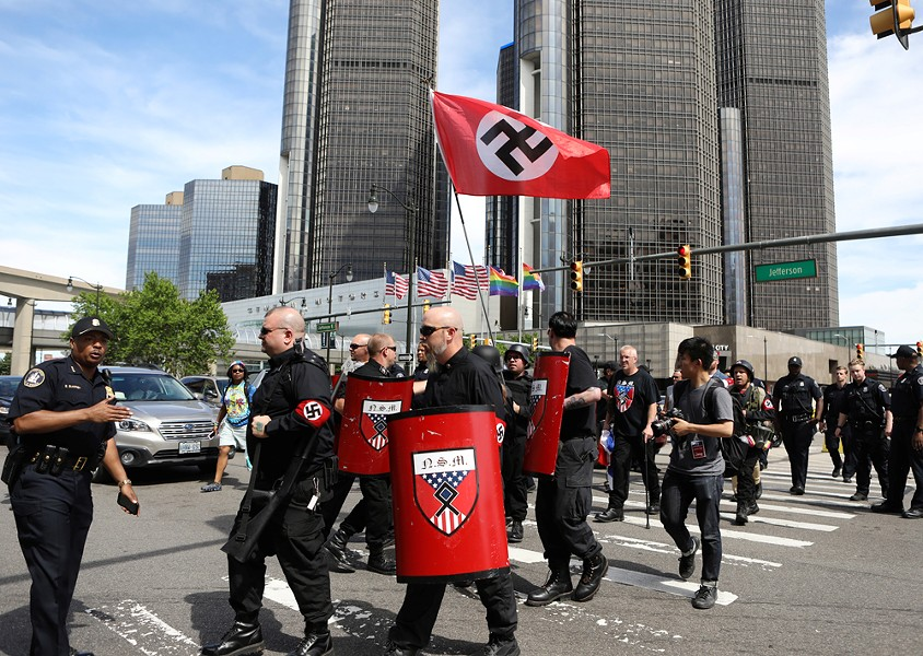 Emboldened by Trump? Members of the National Socialist Movement march with a Nazi swastika flag at Motor City Pride. - JIM URQUHART
