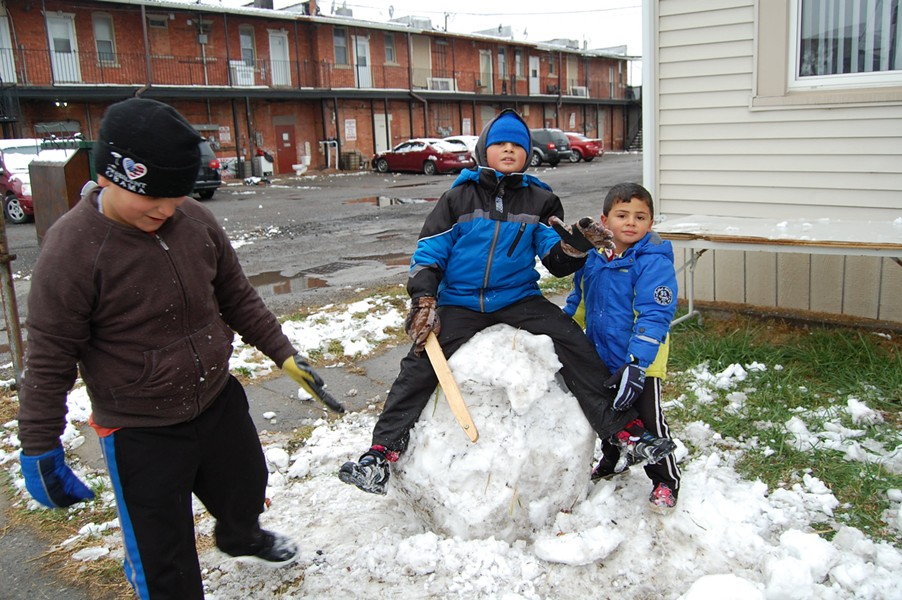 Alrashdan's children playing in the season's first snow, a novelty they relish in a way no lifelong Michigander ever would. - DON JORDAN