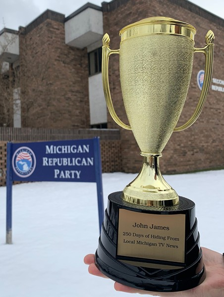 """Democrats show off a trophy that reads, """"250 Days of Hiding From Local Michigan TV news. - MICHIGAN DEMOCRATIC PARTY"""
