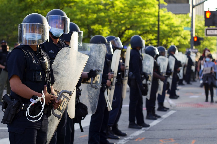 Detroit police clad in riot gear form a barricade outside Public Safety Headquarters. - STEVE NEAVLING