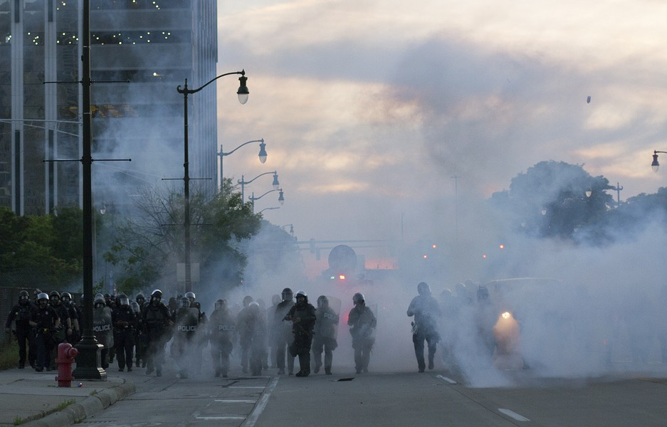 Detroit police deploy tear gas and rubber bullets as protesters flee. - STEVE NEAVLING