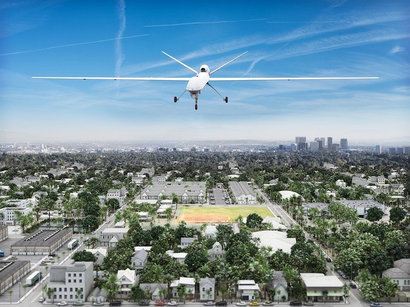 Surveillance UAV drone flying over a residential neighborhood. - SHUTTERSTOCK