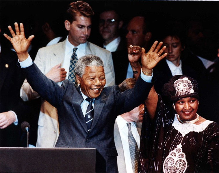 """Amid impassioned cries of """"Amandla!"""" and """"Viva Mandela!"""" Nelson and Winnie Mandela wave to a crowd of more than 49,000 people at Tiger Stadium June 28, 1990. - D. WEISS/WALTER REUTHER LIBRARY"""