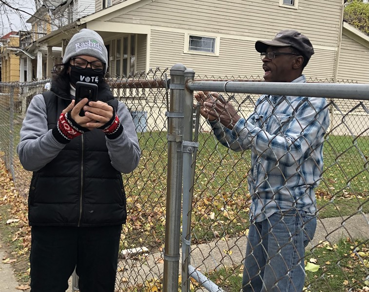 Rashida Tlaib helps one of her constituents navigate the unemployment system while knocking on doors on Sunday. - LEE DEVITO