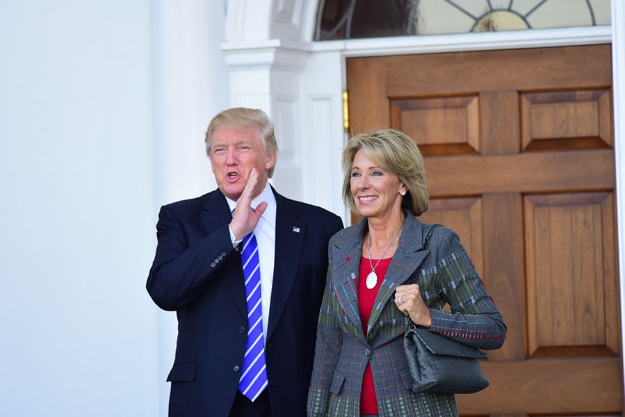 Then-President-elect Donald Trump meets with Betsy DeVos in Bedminster, N.J. in 2016. - A. KATZ