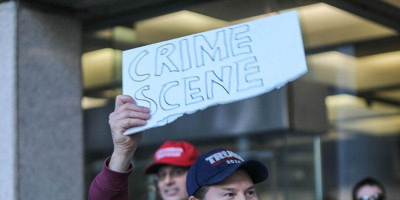 A Trump supporter wielding a sign alleging voter fraud outside of Detroit's TCF Center.