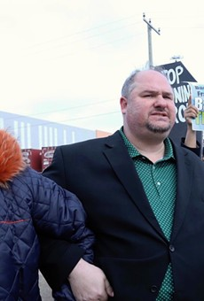 State Rep. Isaac Robinson (center) locks arms with state Rep. Jewell Jones (left) and Imam Salah Algahim (right) as they march from a nearby school to protest US Ecology on Detroit's east side.