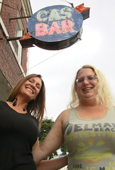 Cas Bar regular Stacie Goolsby and bartender Jodie Welbes pose underneath the bar's weathered sign.