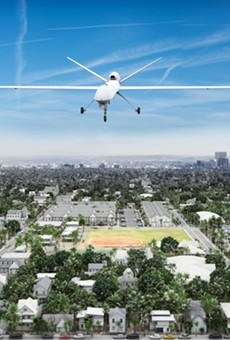 Surveillance UAV drone flying over a residential neighborhood.