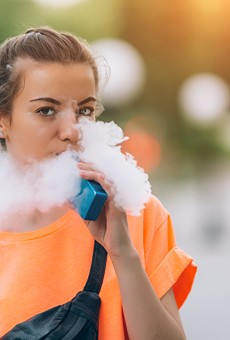 A young woman vaping nicotine.