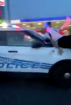Screen grab from a video of a police car plowing through a group of protesters.
