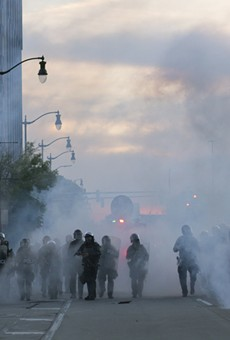 Detroit police deploy tear gas and rubber bullets as protesters flee.