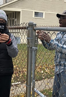 Rashida Tlaib helps one of her constituents navigate the unemployment system while knocking on doors on Sunday.