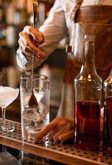 A bartender makes cocktails.