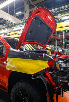 A worker installs a headlight assembly at GM's Chevrolet Silverado and GMC Sierra pickup truck plant.