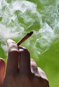 A person smoking a marijuana joint.