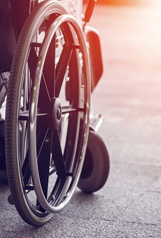 A local activist in a wheelchair has filed suit against a municipal lawyer over demeaning emails.