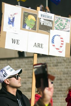 A protester holds a sign referencing the QAnon conspiracy theory at a rally for President Donald Trump in Detroit.