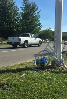 "A ""ghost bike"" shrine memorializes a cyclist killed on Warren Avenue near the Chrysler Service Drive."