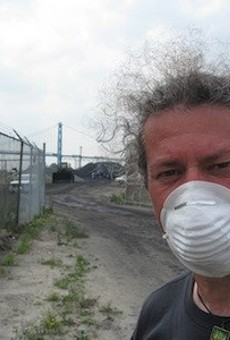 A protester stands in front of the piles of petcoke that graced the riverfront in 2013. The piles are now illegal.