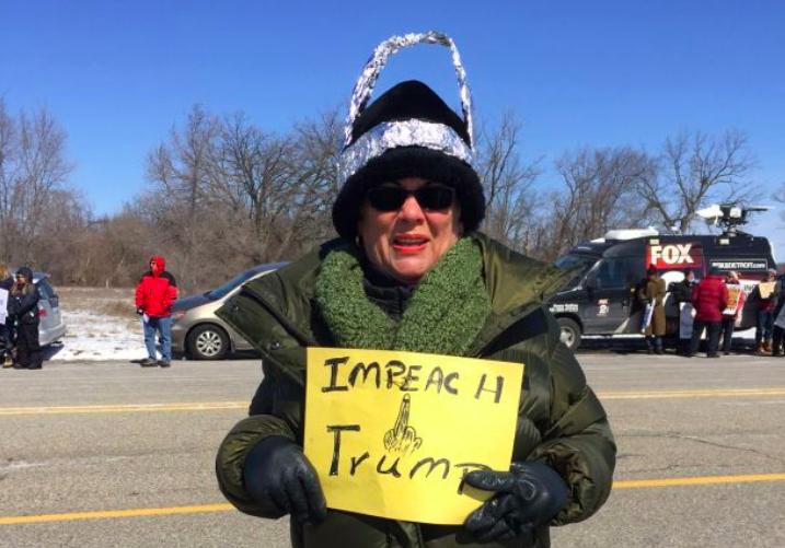 Woman in a tin hat protesting Trump's visit to Ypsilanti last year. - VIOLET IKONOMOVA