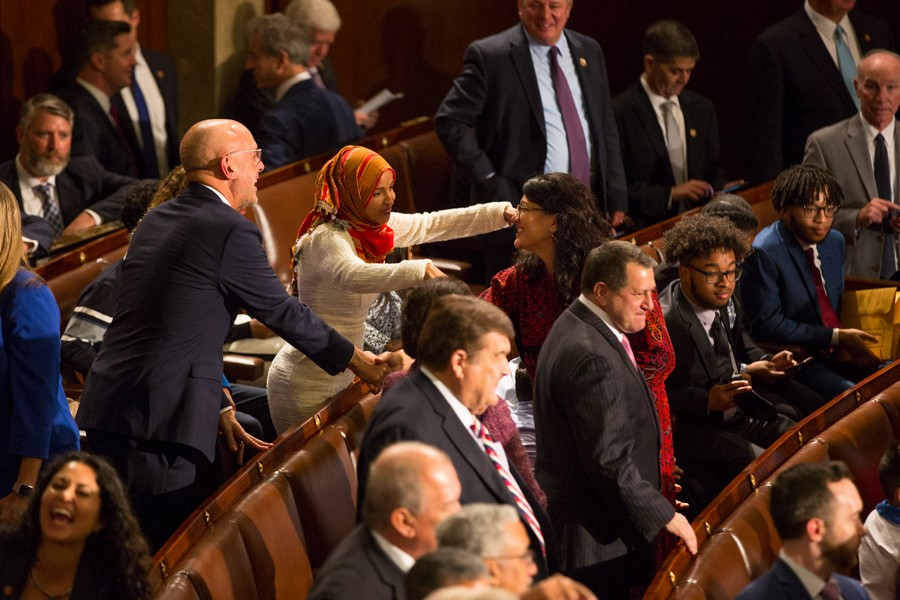 Rep. Ilhan Omar, the only other Muslim woman elected to Congress, reaches out to hug Tlaib as Pelosi concludes the ceremony. - ERIK PAUL HOWARD