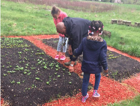 Marc Peeples working with children on Liberated Farms. - PHOTO COURTESY OF LIBERATED FARMS