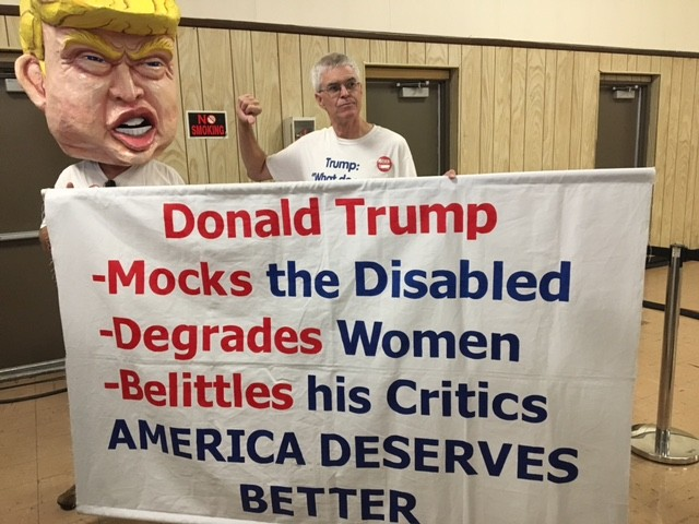 The Bernie Sanders event in Dearborn is warming up with Tom Moran, 61, a retired bus driver from Fenton, MI. He's been traveling the country protesting Trump. - PHOTO BY COLIN MALONEY.