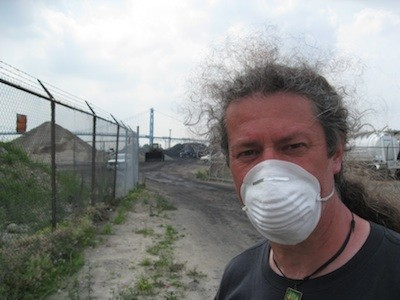 A protester stands in front of the piles of petcoke that graced the riverfront in 2013. The piles are now illegal. - PHOTO BY CURT GUYETTE
