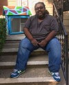 James Chism, Harper Woods resident and participating artist in the Little Library prize, sits with the library he painted, called <i>Breaking Barriers, Smashing Ceilings.</i>