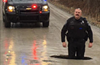 A Grand Blanc Township police officer stands knee deep in a pot hole on McWain Road.