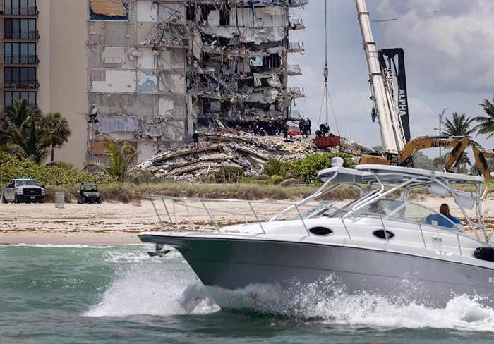 A boat passes off shore as members of the South Florida Urban Search and Rescue team look for possible survivors. - PHOTO BY JOE RAEDLE/GETTY