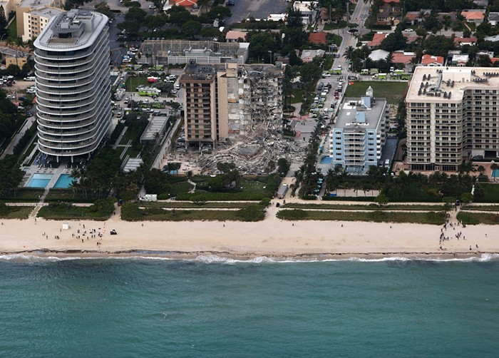 Miami architect Kobi Karp was initially involved in the plans for the 8701 Collins Ave. highrise (far left) just to the south of Champlain Towers South. - PHOTO BY JOE RAEDLE/GETTY