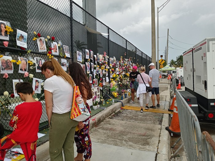 Visitors and residents of Surfside pay their respects to those lost in the Champlain Towers South Collapse at a memorial wall on Monday, June 28. - PHOTO BY JOSHUA CEBALLOS