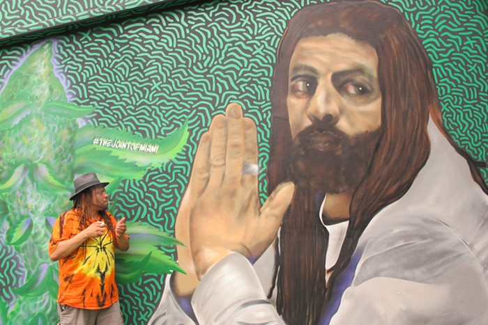 NJWeedman sparks a joint while standing in front of a mural of himself. - PHOTO BY NATALIA GALICZA