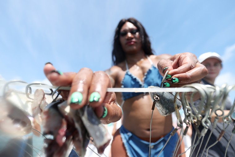 Miss Toto prepares the fishing lines with bait. - PHOTO BY CLIFF HAWKINS