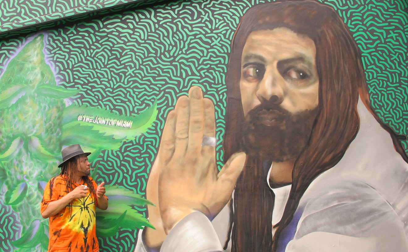 NJWeedman sparks a joint while standing in front of a mural of himself.