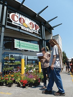 PHOTO BY RYAN BURNS - A Co-op shopper signs a petition supporting living wages and affordable health care for employees.